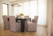 Dining chairs slipcovered in Sunbrella Frequency Ash. Decorative pillows and runner in Sunbrella Icon Mystique.
