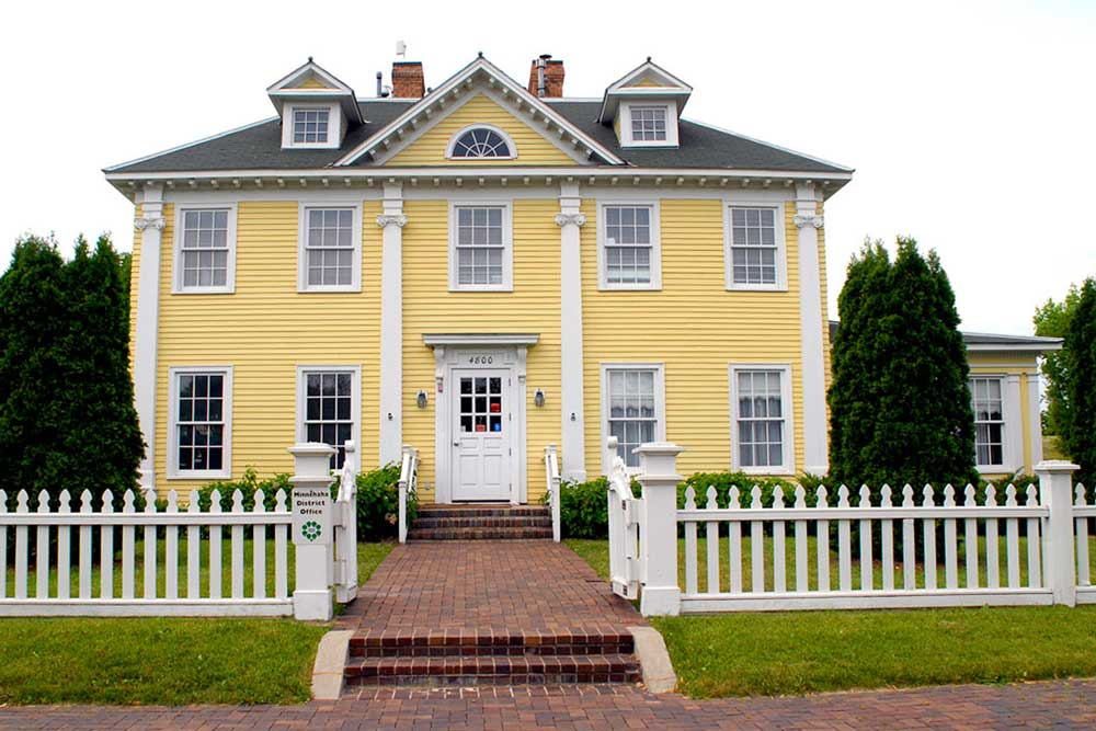 The Frontside Of A Longfellow House Shows White Picket Fence Outside Large
