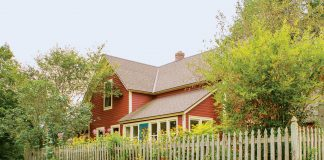 Lynn Steiner's 1898 red farmhouse is surrounded by lush and colorful greenery.