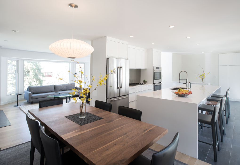 A sleek and modern kitchen is highlighted by a white, central island, white cabinetry and stainless steel appliances. A dark wood dining room table is adjacent to the island and is surrounded by black chairs.