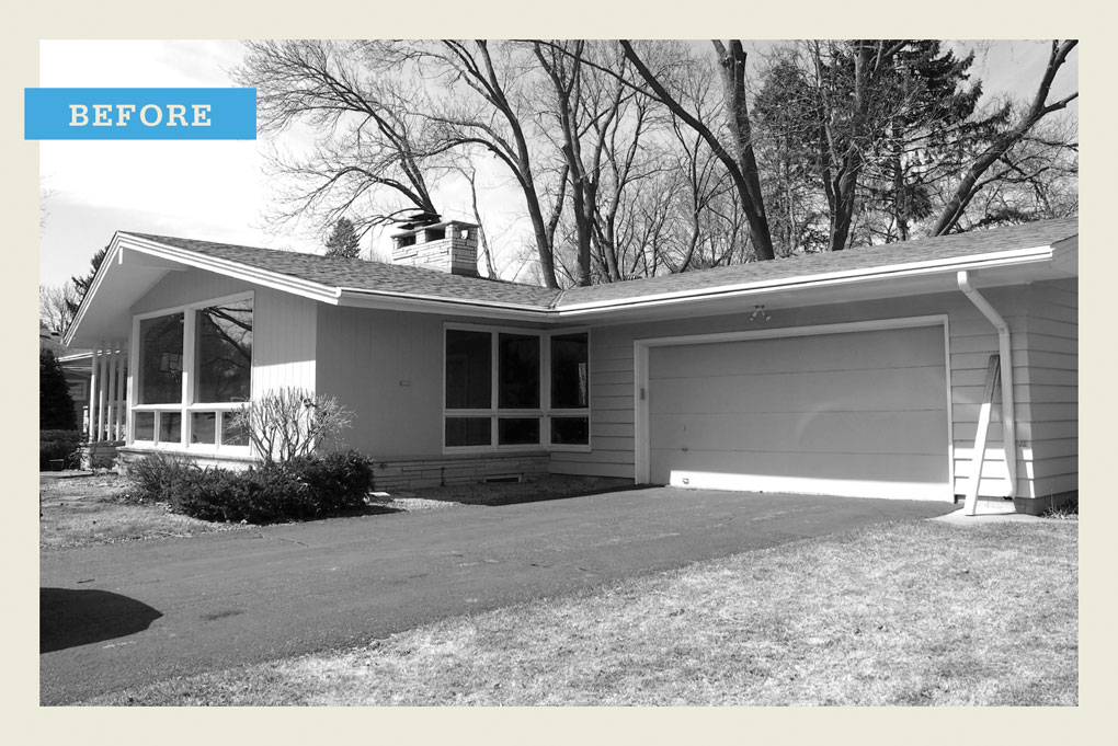 """A black-and-white """"before"""" photo of rambler that featured large bay windows and attached garage."""