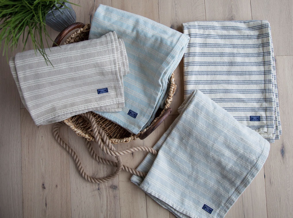 A collection of blankets by Fairbault Wooden Mill laying on the floor.