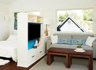 A small living and bedroom separated by shelving.