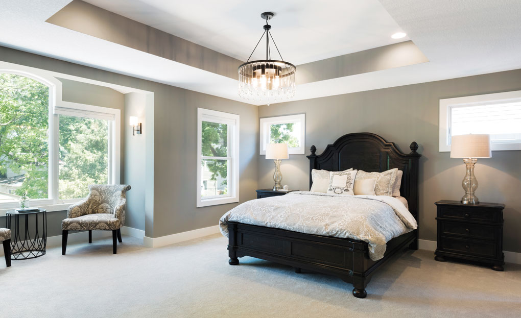 A master bedroom with a chandelier hanging over the bed and a private seating alcove.