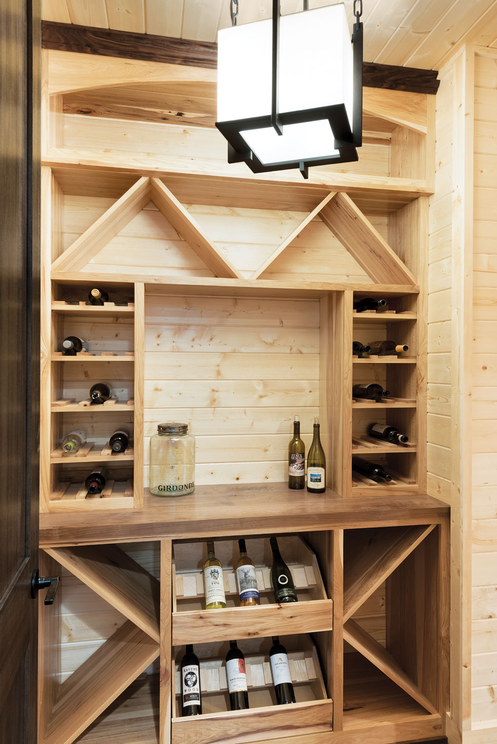 A knotty pine- and hickory-lined wine cellar stocked with bottles of wine.