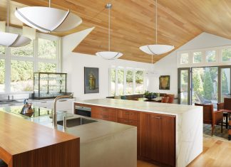 A clean-lined and modern kitchen that features a center island, stainless steel appliances and light wood in both the flooring and ceiling.