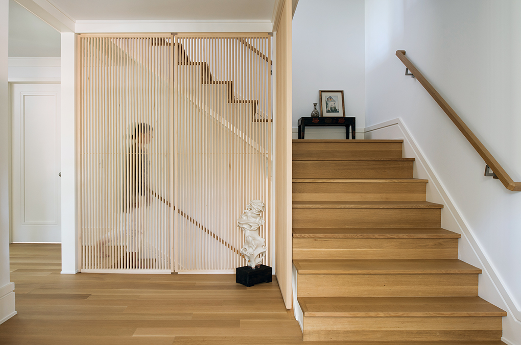 A white oak staircase leads to the second level. Next to it is a pale wooden screen semi-hiding a staircase leading to a lower level.