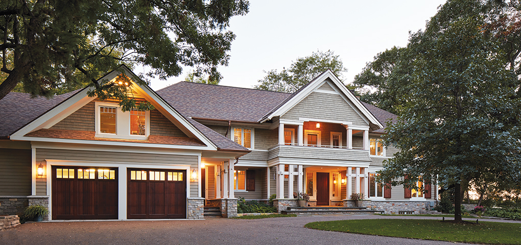 An exterior of a home features shingle-style and clapboard siding, gable roofs, and porches giving the house a lake-cottage aesthetic.