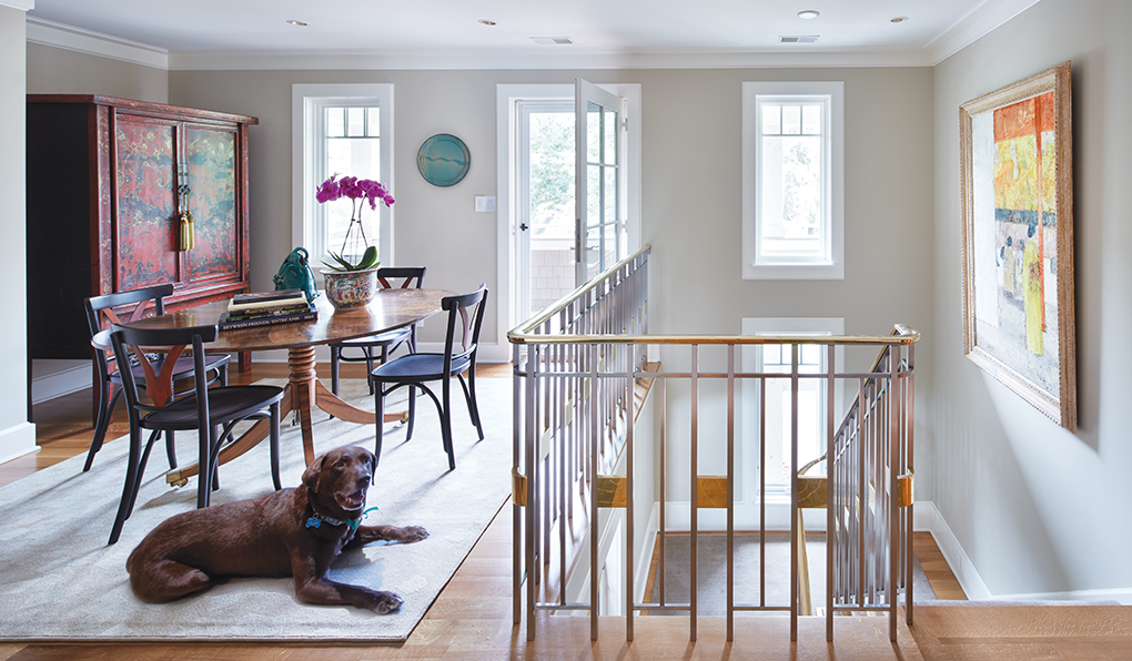 The second level of a home shows a unique brass and steel railing, table and chairs, and the family dog.