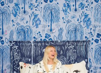 A portrait of Kate Worum sitting on her bed surrounded by blue wallpaper of her own design.