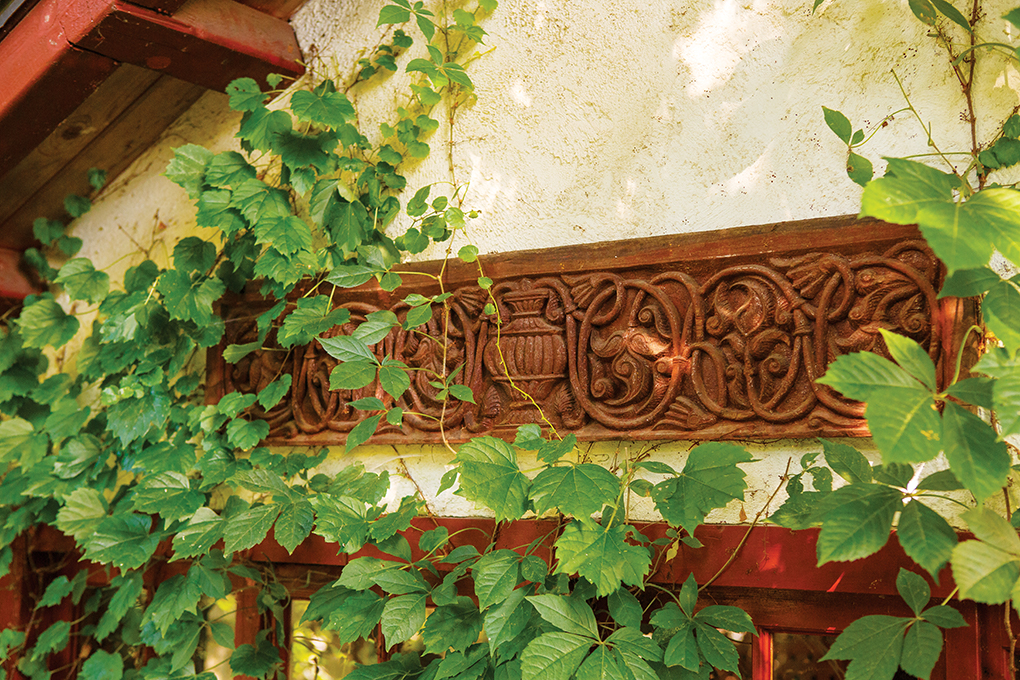 A hand-carved teak piece sits above a garden shed's windows and is covered in ivy.