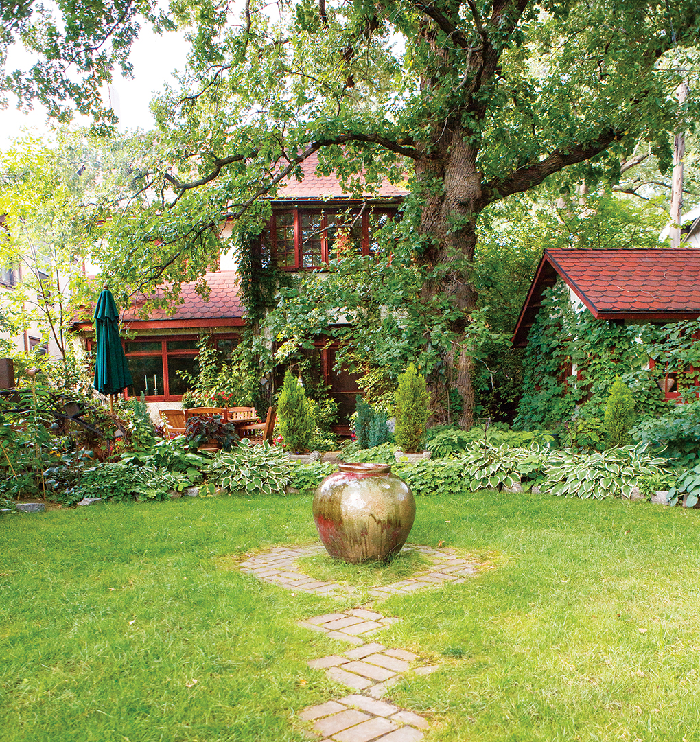 The backyard features a large jar in the center. In the background, a lush garden full of greenery surrounds the home and garden shed.