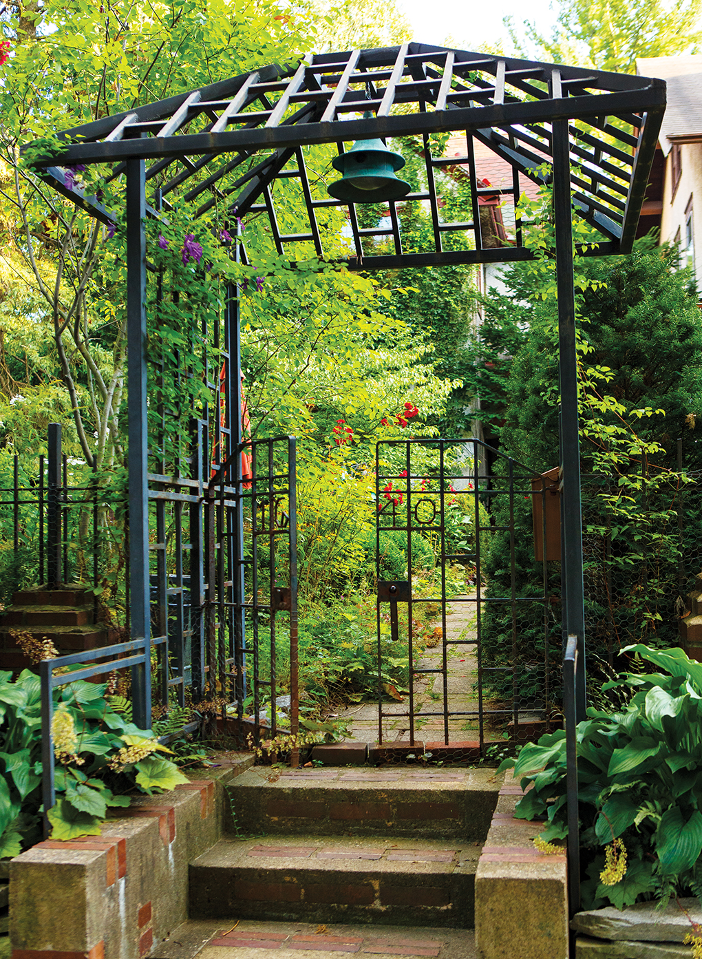 A gate leads to a lush and green garden.