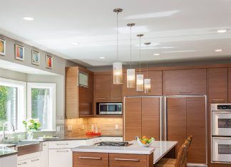 A large kitchen with a center island with lights hanging over it, and light-wood cabinetry accented by stainless steel appliances, a winner in the 2017 National Kitchen and Bath Association Design Awards.