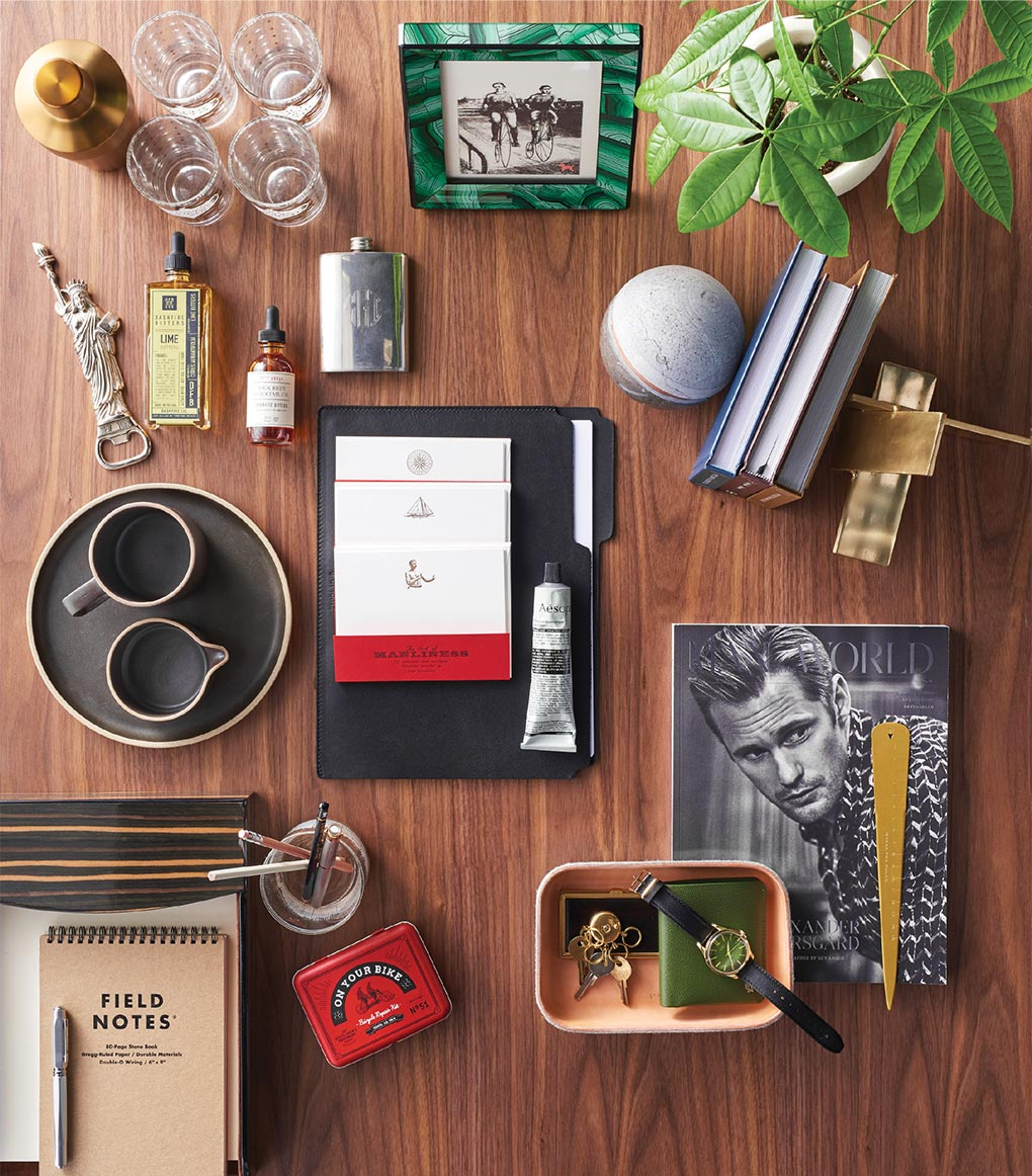 A wood table with holiday gift ideas covering it, including a cocktail shaker, stationery, assorted books, leather folder, hand balm, brass bookend and more.