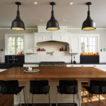 White kitchen with black chairs and brown table