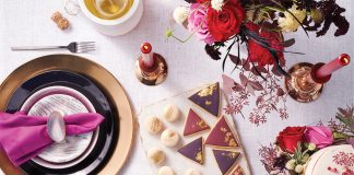 A table decorated with holiday gift ideas, including black plates and flatware, purple salad plates, deep-cut crystal goblets, white marble cheese plates, candles, flowers and more.