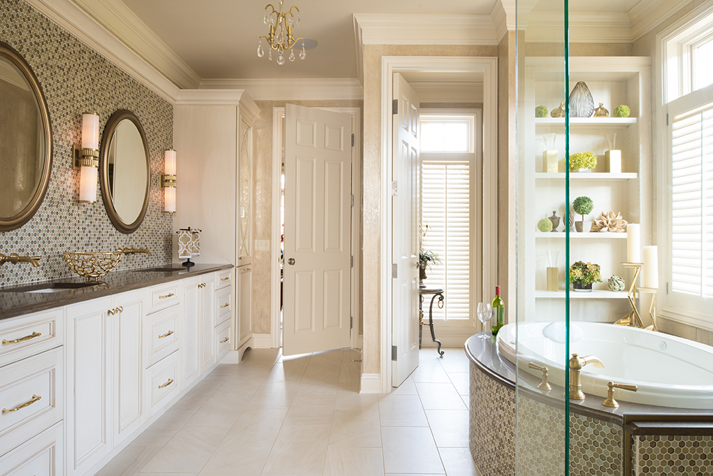 A white bathroom with gold hardware, two sinks with accompanying mirrors, and large soaking tub.