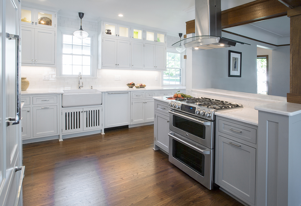 A white kitchen with stainless steel appliances, and a large stainless steel range hood.