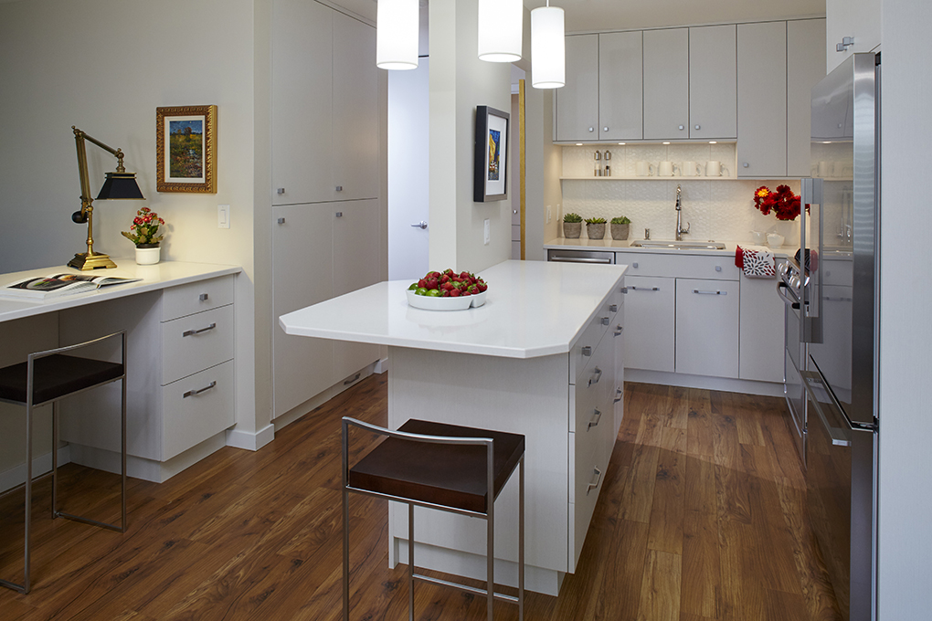A small, white kitchen featuring center island, stainless steel appliances and hardwood flooring. A bowl of strawberries sits on the center island, and an open book with desk lamp sit atop a nearby desk.
