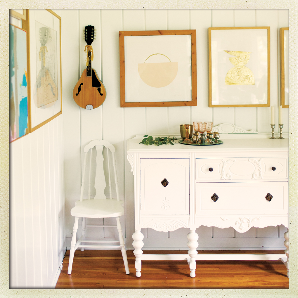 White kitchen with two frames and a mandolin mounted on the wall.