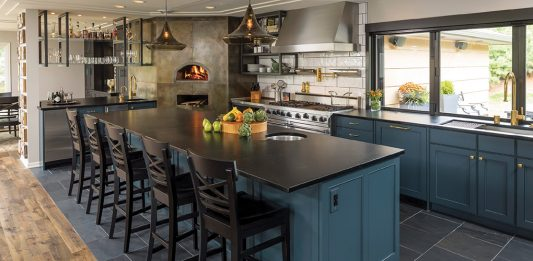 A blue kitchen with large wood-fire grill built by Shelter Architecture.