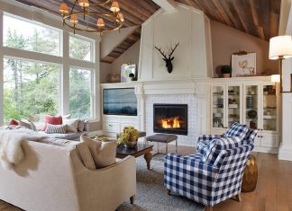 Living room with fireplace and deer head on mantle and checkered ottoman