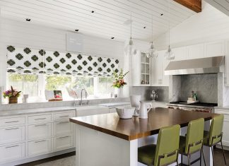 An all white kitchen with green chairs surrounding the center island.