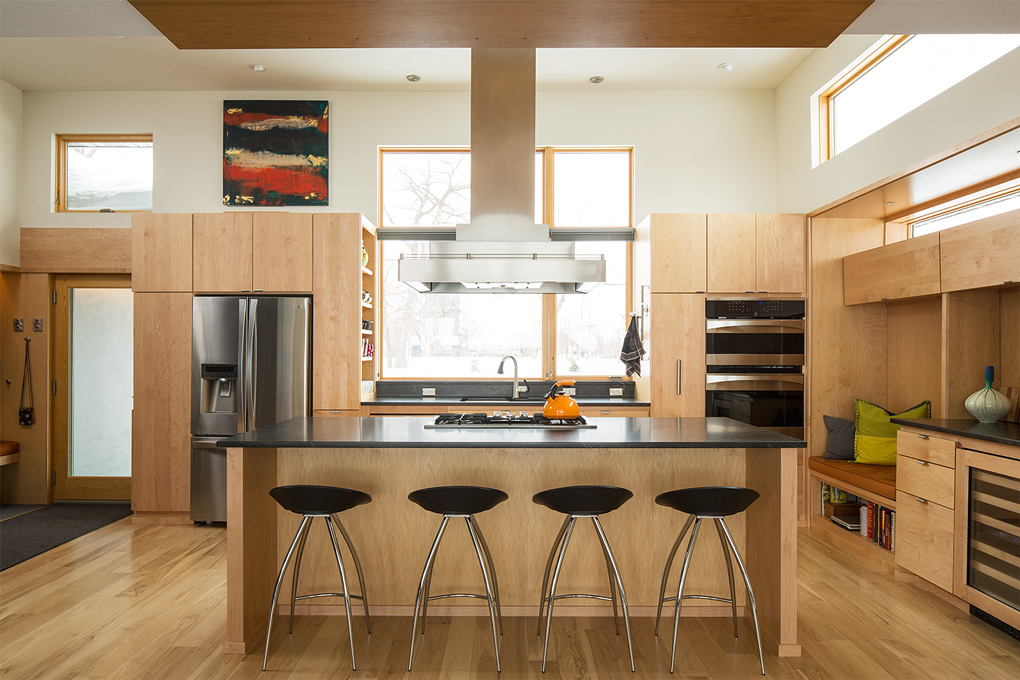 An all wood kitchen with stainless steel appliances designed by Eric Odor.