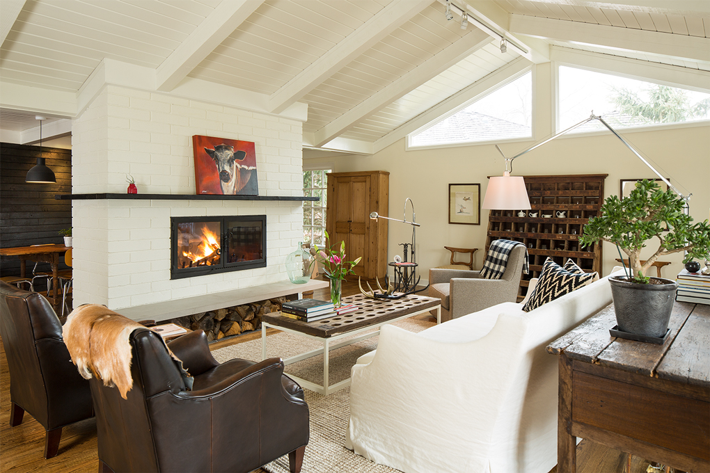 An open living room with seating surrounding a coffee table and lit fireplace.