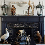 Taxidermy and lamp lanterns decorate a darkly painted fireplace.