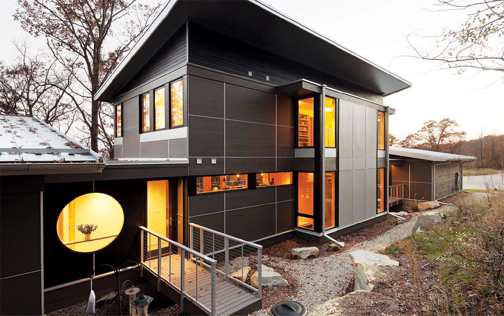 A modern and darkly colored home with lights on inside designed by Eric Odor.