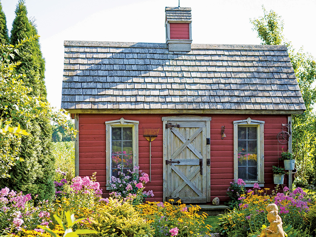 The red garden shed is the backdrop for a large English garden with a statue of cherubs at its center.