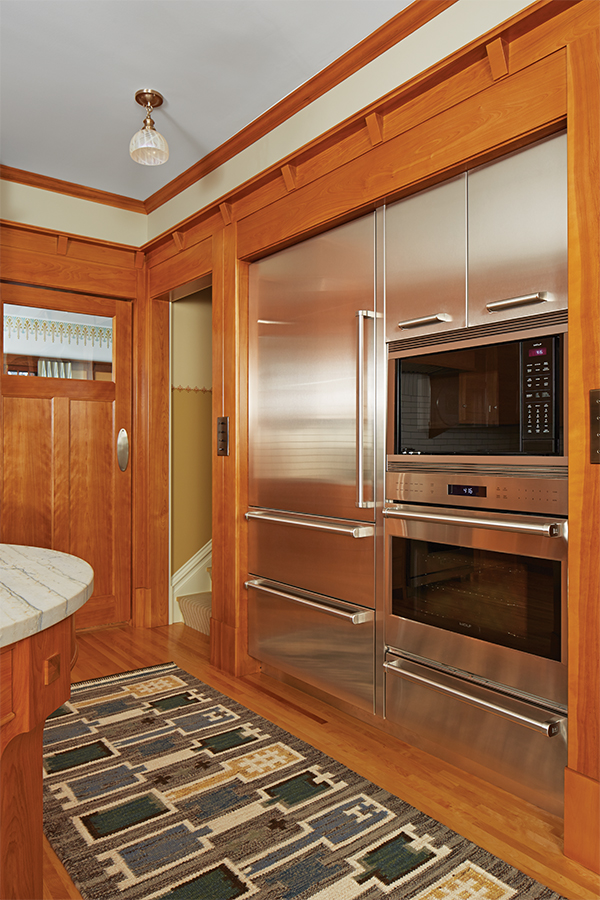 Stainless steel appliances surrounded by light wood cabinetry in a kitchen designed by David Heide Design Studio.