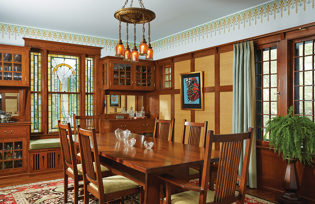 Designed by David Heide Design Studio, the dining room's oak paneling and molding was restored according to Ellerbe's original drawings. The cabinetry, art-glass windows and sidelights, and stenciling emphasize the room's historic style.