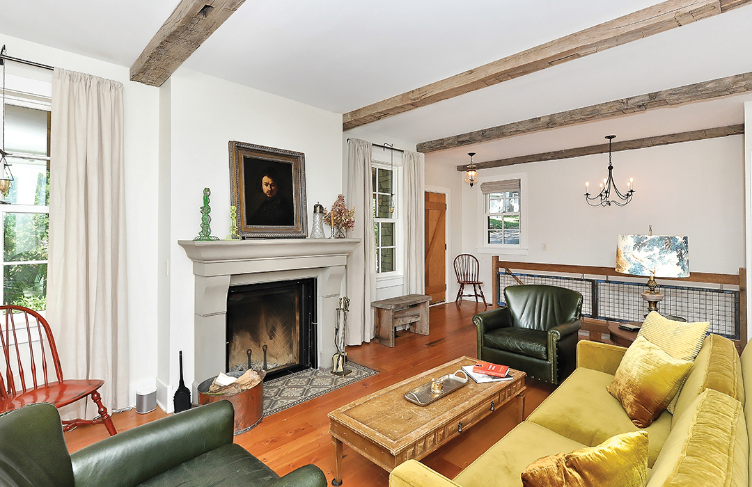 Vintage treasures capture the feel of a mid-19th century home. Both the floor and the mantel are made from recycled materials in a living room designed by Studio Hittle.