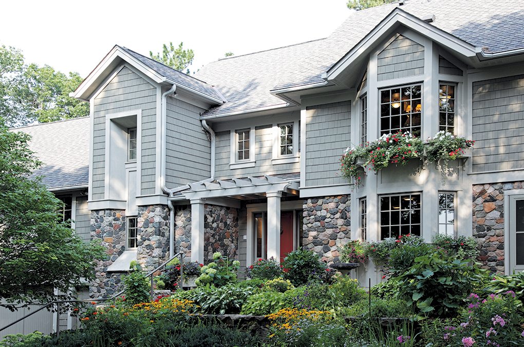 The exterior of a two-story home with plenty of green landscaping and plants out front.