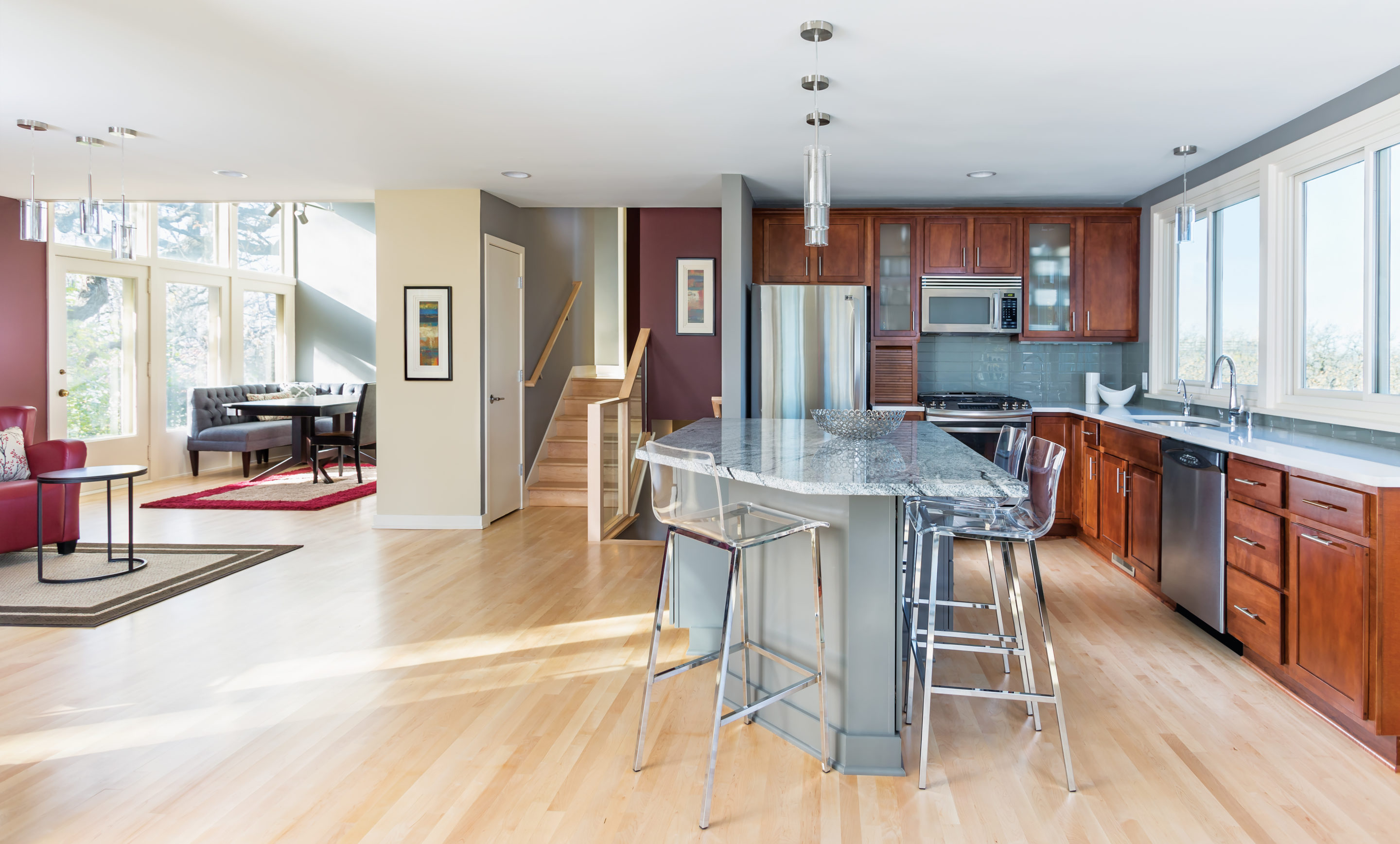 A remodeled kitchen by Close Associates features modern finishes and a large, granite-topped island.