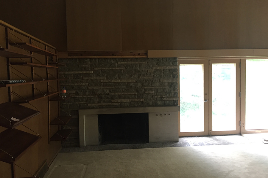 "A ""before"" photo of a living room with a fireplace before it was remodeled by Bella Custom Homes."