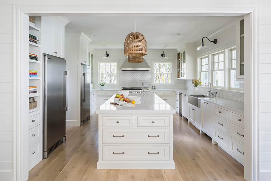 The entrance to an all-white kitchen with light hardwood floors and stainless steel appliances.