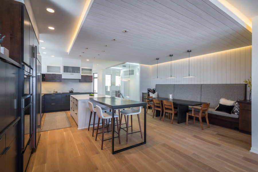 Photo of a modern kitchen and living space with wood floors remodeled by Revolution Design Build.