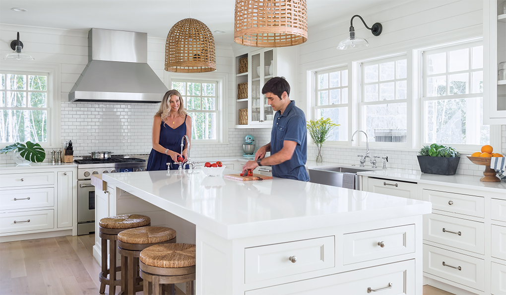 Stacy and Michael Sullivan work in a kitchen designed for multiple cooks and visitors. Framed by windows, the range and vent hood are a focal point.