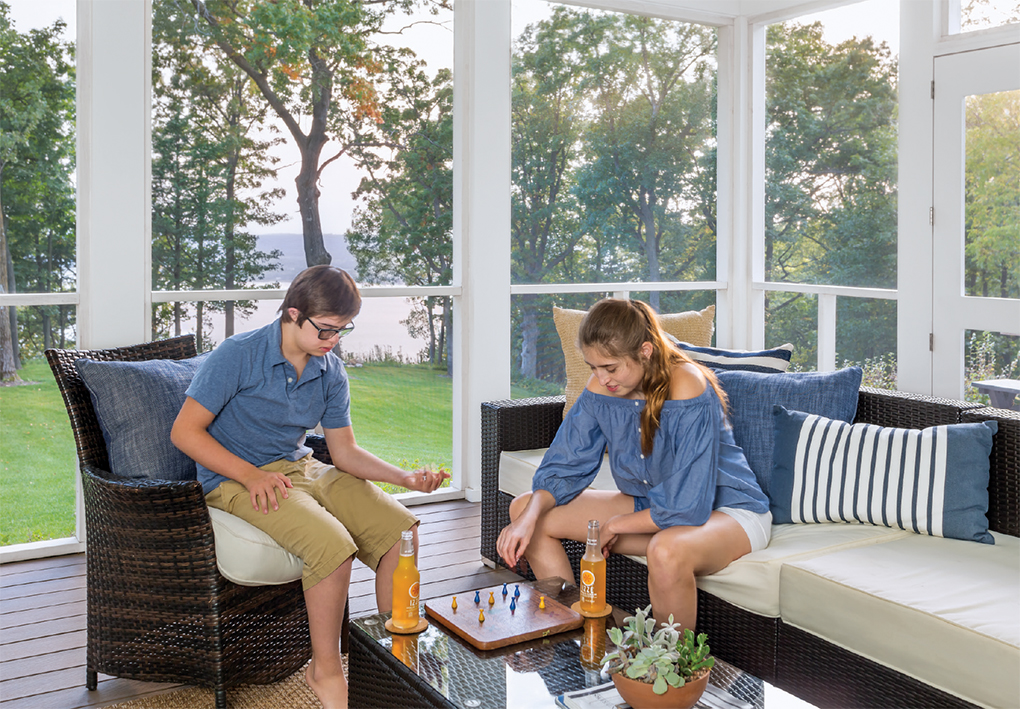 Two kids sit at a table in a screen porch playing a board game.