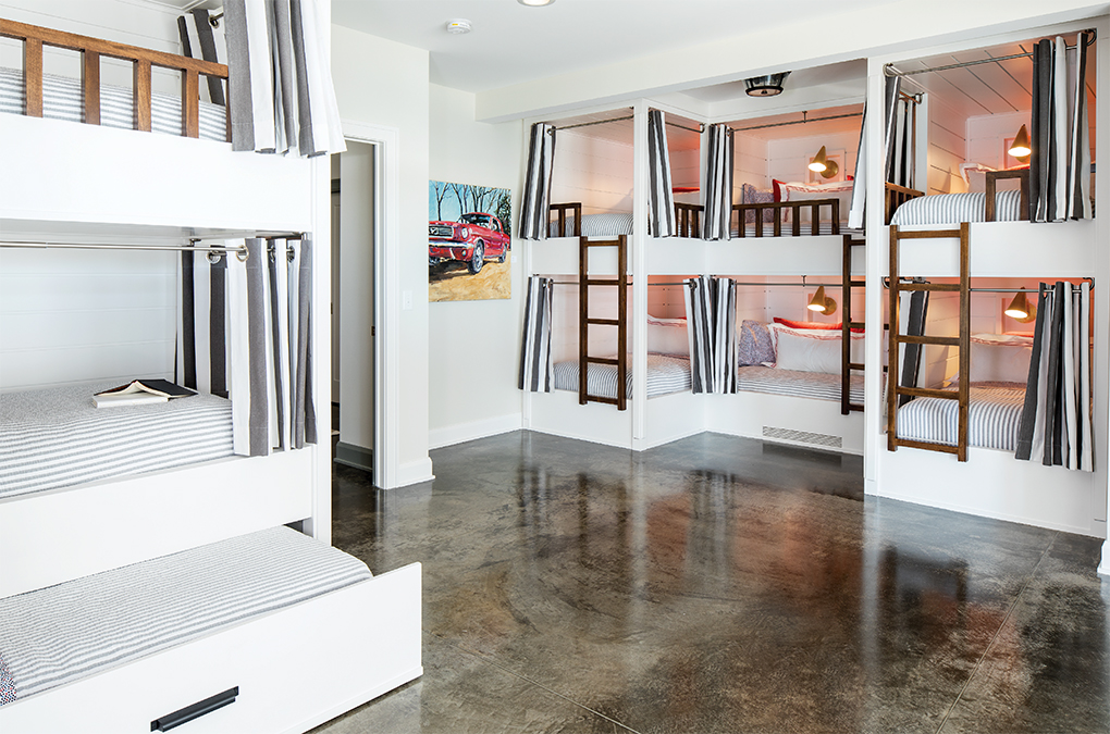Cleverly outfitted bunk beds in the basement give kids privacy as well as their own lights and USB ports. Polished concrete floors are finished with a bit of grit to keep wet feet from slipping.