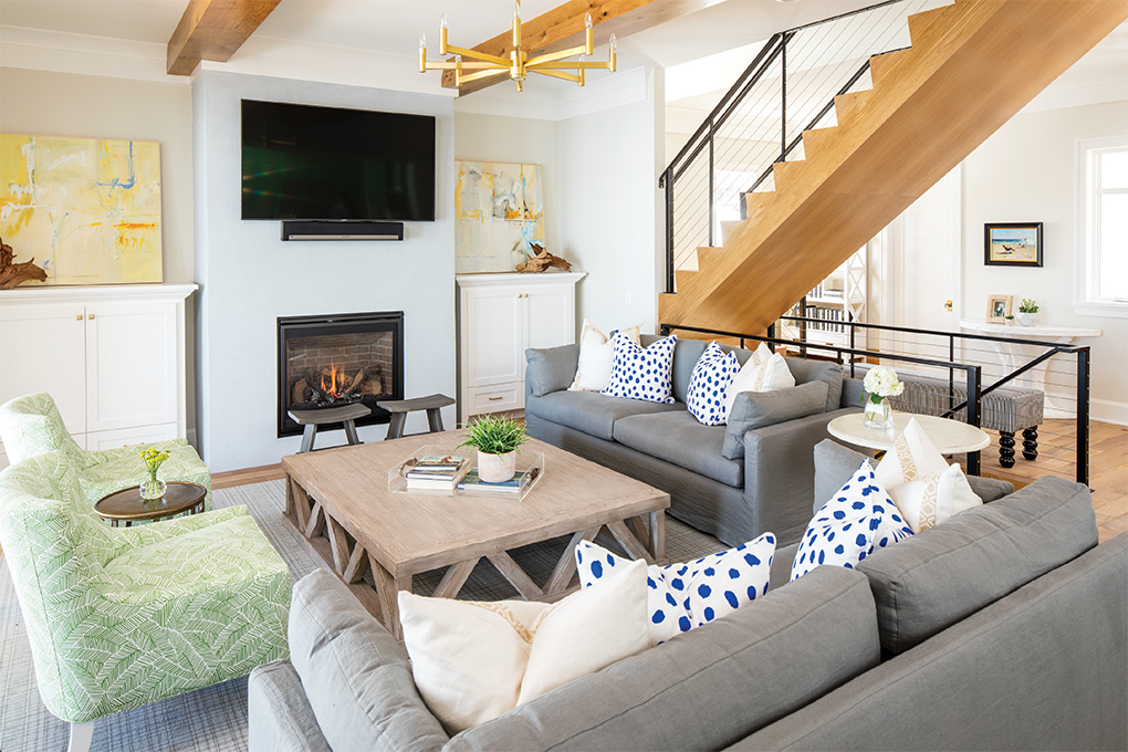 The family room features loads of comfy seating. A suspended white oak staircase, and black metal and cable railings add modern flair to the space.