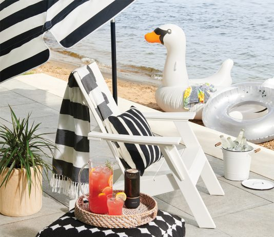 A white deck chair with a tray of beverages and umbrella next to water.