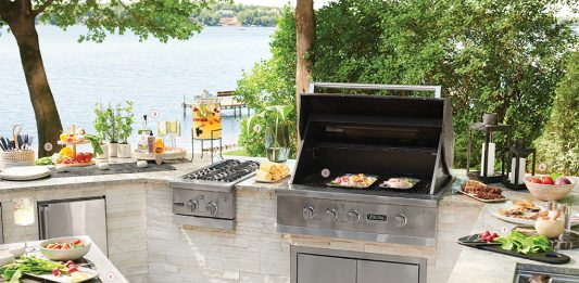 An outdoor kitchen with stainless steel grill, plates of food, and a table.